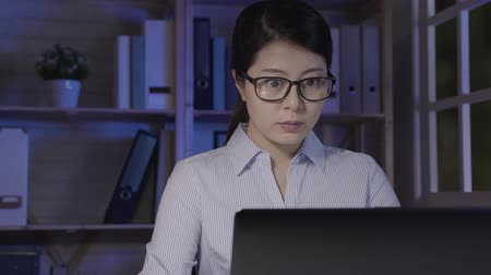 kalmak : Casual suit beautiful woman working on a laptop at the night at home. young asian office lady stay up late using notebook computer doing project for job. girl in glasses concentrated typing keyboard