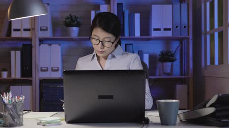 tartózkodás : fast motion of young asian businesswoman talking on phone with colleague discussing problems on work. lady using laptop while over working in a dark office at night. girl in glasses writing on book.