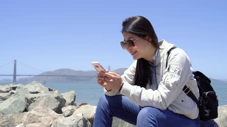 в чате : travel backpacker resting on rock searching information on cellphone on internet while sightseeing outdoor golden gate bridge in san francisco. young girl traveler sitting on stone near bay summer.