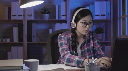 özel öğretmen : slow motion asian student girl using online education service at home at late night. Young woman looking in laptop display typing keyboard watching training course and listening it with headphones.