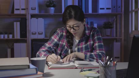 bekap : fast motion of female college student calculating and handwriting notes with pen. young girl writing on notepad in midnight working hard in dark room at home. beautiful asian woman study for exam. Stock mozgókép