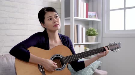 usual : Excited young female player sitting on modern sofa playing acoustic guitar. girl enjoy the song she made by instrument. beautiful music woman usual lifestyle concept.
