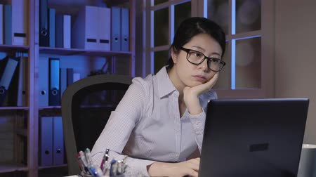 tartózkodás : fast movement tired asian woman working late at night. office lady using laptop computer hand touching chin stressful life and deadlines concept. thoughtful girl coming up new idea doing project Stock mozgókép