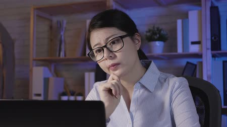 kalmak : Attractive young woman working on coworking office at night. Girl using laptop computer thinking new idea of season sale project. thoughtful asian lady in glasses hard working in midnight. Stok Video