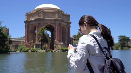 pilares : happy asian girl traveler visiting palace of fine arts taking photo by cellphone camera app. woman tourist using smart phone take pictures old history building in san francisco california usa.