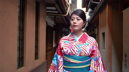 hanamikoji : quick motion of young girl tourist experience local japanese culture wearing kimono costume walking in famous tourist attraction in kyoto japan. female in traditional colorful dress hanamikoji street