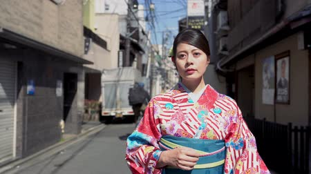 hanamikoji : young local japanese lady elegant confident in kimono dress walking on urban city street on sunny day. beautiful woman wearing traditional costume going to visit family new year celebration festival