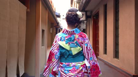 hanamikoji : fast forward of young japanese girl in kimono dressing walking in the path to festival. back view lady in colorful beautiful traditional costume going pass by the house wooden door in hanamikoji dori Stock Footage