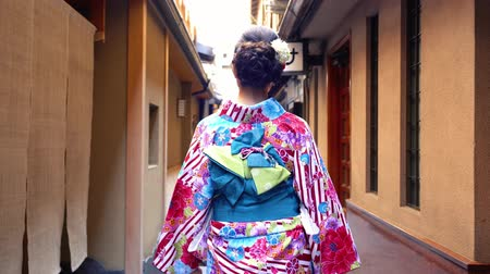hanamikoji : back view of young japanese girl in colorful kimono walking in path. female in traditional costume going to join festival in summer under sunshine. beautiful elegant lady in hanamikoji dori.
