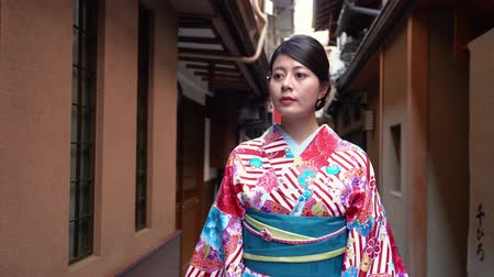 hanamikoji : elegant beautiful kimono dressing traveler girl walking along in little path in japan. young japanese lady wearing traditional costume seeing around in hanamikoji dori in kyoto japan. Stock Footage