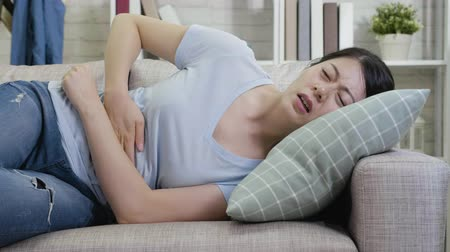 diarrhea : slow motion of young woman with stomach ache lying on couch in apartment. housewife feeling painful suffering from abdomen hurt. sick lady resting at home pain belly hands holding.