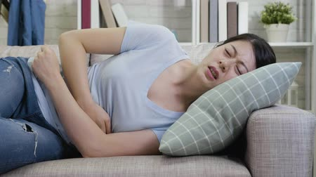 the inflammation : Young lady frowning touching massage belly lying on sofa in living room at home. asian housewife suffering from abdominal pain with head resting on pillow on couch. girl feeling painful stomach ache