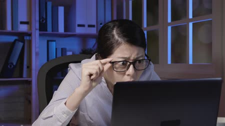 exaustão : slow motion of tired young woman burning midnight oil. asian office lady working late at night on her laptop computer sitting at desk holding glasses shaking head trying to stay focused eyes looking.