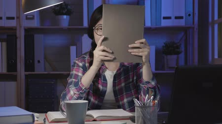 kalmak : slow motion of asian girl student smile and hides her face behind a book sitting at desk at home in midnight. female laughing cheerfully wearing glasses stay up late studying hard at night.
