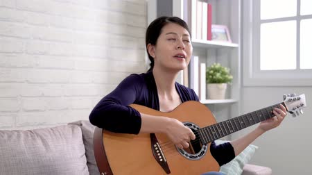 home studio : slow motion attractive musician young woman sitting in the living room playing acoustic guitar and singing songs. Teenager holding instrument on sofa enjoy relax. happy music girl lifestyle concept
