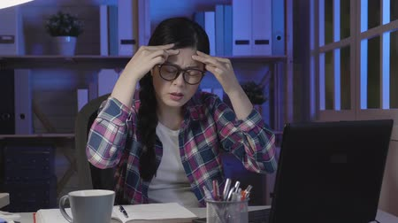 mračící : slow movement young college girl stop typing keyboard doing project in midnight shaking head release painful of headache sitting at desk. asian woman frowning closing eyes feeling unwell at night.