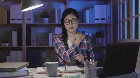 krk : slow motion asian woman with neck pain after long hours of doing homework studying for test. young college girl massage shoulder sitting at desk prepare for test in midnight in dark room at home.
