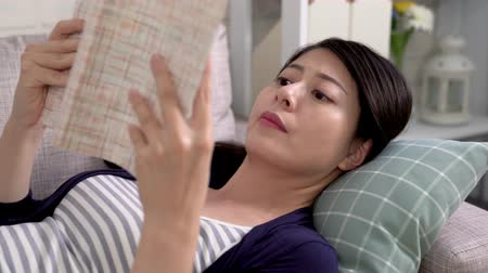 apartament : fast motion of young asian woman lying on couch reading novel feeling bored waiting for husband coming back to home in daytime. wife bored relaxing time dislike books. Boring literature concept
