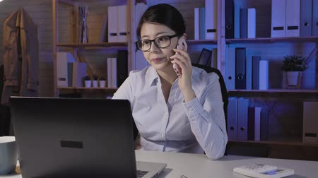 kalmak : fast motion young businesswoman talking on smart phone wearing glasses looking notebook computer screen at late night work. office lady working at night calling coworker discussing problem on laptop Stok Video