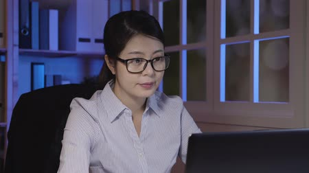 tartózkodás : slow movement of young female asian business woman working in company. office lady works late into night looking at laptop computer monitor. girl in glasses concentrated typing on notebook do project Stock mozgókép