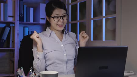 végre : slow motion of smiling Asian woman using laptop at night in office finish work. freelance working late in company finally done well stretching raising hands arms cheerfully. positive manager resting.