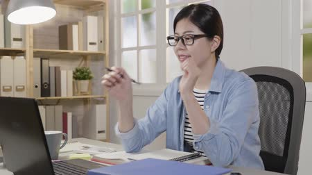 хмурый : slow motion thoughtful asian woman smiling doing project at home. young college girl student with glasses confident typing homework on laptop computer sitting at desk satisfied with work in morning