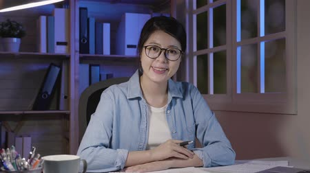 camera move : slow motion of confident young girl worker face camera smiling confident in home office staying up late working. asian lady holding pen sitting at desk in dark room place in apartment near window.