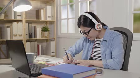 репетитор : slow motion girl in headphones watching webinar listening to web audio course making notes and writing important information. Happy student enjoy taking e-learning class remote studying concept. Стоковые видеозаписи