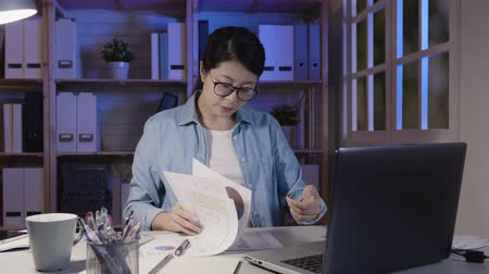 superior : slow motion of focused asian woman in glasses looking at laptop computer screen monitor sitting at desk in home office at night. girl soho freelance worker hard working staying up late in midnight. Vídeos