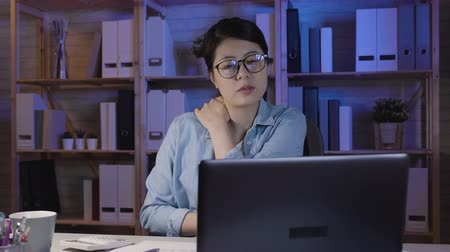végre : slow movement of young asian woman working with laptop computer late in office suffering from neck pain massage shoulder. beautiful soho lady in glasses stay up late hardworking at home use notebook.