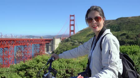 Франциско : happy carefree asian woman tourist visit golden gate bridge talking to friend partner in bike tour. young girl telling boyfriend come closer moving hands giving attractive smile on bicycle outdoor.