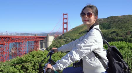 здесь : young girl backpacker passion invited friends join her trip by bicycle visiting golden gate bridge sightseeing on sunny day. asian woman traveler riding bike not alone. beautiful lady with sunglasses Стоковые видеозаписи