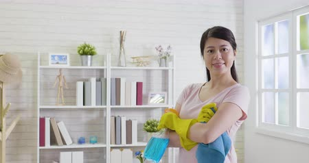 püskürtücü : slow motion of attractive beautiful asian woman maid smile and cross arm feeling so happiness and confident. cleaning Service concept. young housewife in yellow protective gloves holding sprayer rug Stok Video