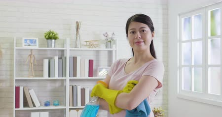 temizleme maddesi : slow movement young female housekeeper face camera smiling attractive standing in bright cozy room at home. asian wife ready to do housework in the daytime. girl housekeeper cleaning up apartment Stok Video