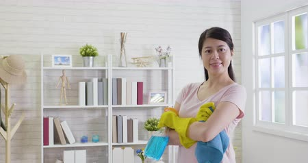 sterilization : Smiling young woman worker holding cleaning spray and cloth.young housewife cross arms face camera with confident looks. asian woman in casual tidy up living room in morning in the daytime.