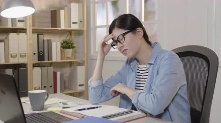 bolest hlavy : slow motion young college girl massage temples feeling dizzy shaking head frowning release painful from head. asian woman in glasses sitting at desk studying prepare for exam feeling unwell. Dostupné videozáznamy