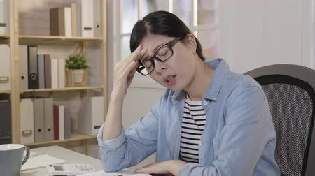 хмурый : Frustrated asian student in glasses studying at desk suffering from severe headache. exhausted college female distracted from final exam having serious tension. Стоковые видеозаписи