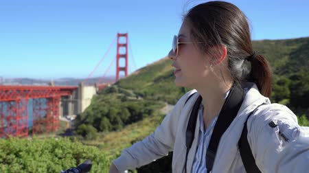 здесь : young college girl tourist holding cellphone on video phone call with family. female local student waving hands to camera and raising showing sharing beautiful view of golden gate bridge on sunny day Стоковые видеозаписи