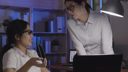 superior : two office lady overtime working in dark night company. asian coworkers with eyeglasses discussing about project on screen monitor laptop computer. female colleague thinking new idea to solve problem Vídeos