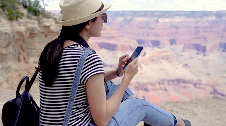 見落とす : girl backpacker hiking in Grand Canyon National Park relaxing searching information online guide book of history desert mountain nature change on smart phone. young asian woman touch screen cellphone 動画素材