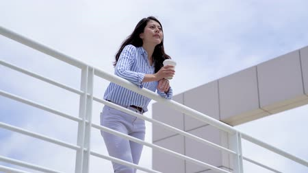 Франциско : asian businesswoman having break on office terrace outdoor drinking coffee. young office lady resting relax in afternoon tea time. girl in smart casual with blue sky in background low angle view.