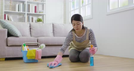 szobalány : slow motion wooden floors cleaning with rag in living room near the sofa couch. young asian housewife wearing apron doing regular clean up. female maid doing housekeeping in apartment wiping by cloth Stock mozgókép