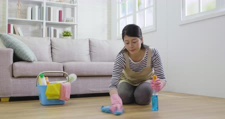 pano : people housework and housekeeping concept. young asian woman in pink rubber gloves with cloth cleaning floor at home near the window in living room. cozy modern simple design couch in apartment.