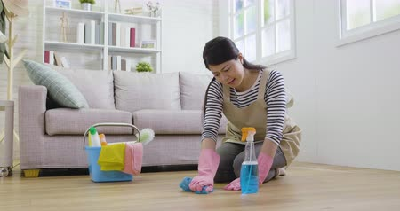 хмурый : slow motion hard female frowning using lot of power in spring cleaning house wiping wooden floor. asian girl in apron with detergent and cloth tidy up doing house chores at home. housewife working.