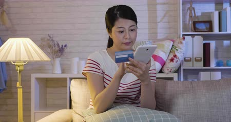 cardíaco : slow motion of elegant house wife purchasing online cloth store shopping paying by debit card relaxing at home at night in cozy modern living room on couch near lamp. girl doing payment on internet.