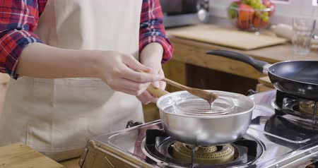 smetanový : slow motion of asian female hand melting dark chocolate in hot pot with boiled water on stove in wooden kitchen. woman in apron holding spoon stirring cocoa cream handmade dessert for valentines day Dostupné videozáznamy