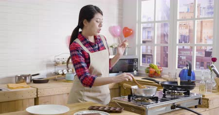 singing bowl : Happy asian young woman singing dancing while cooking in modern wooden kitchen. female in apron with love preparing valentine day surprise. girl with wooden spoon stirring dark chocolate smelling. Stock Footage