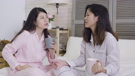 koffie verkeerd : Two female friends sitting together on bed chatting talking and drinking coffee spending time together. young girl in purple pajama listening her roommate complaining life problem in badroom frowning
