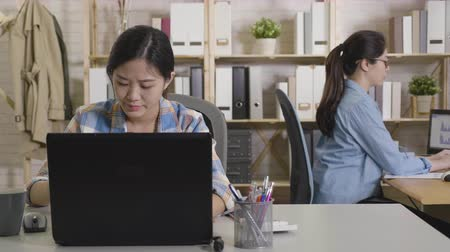 mračící : Young Asian businesswoman frowning with concern as tries to understand something reading on laptop computer. female employee get confused about the work project. elegant co worker in glasses working.