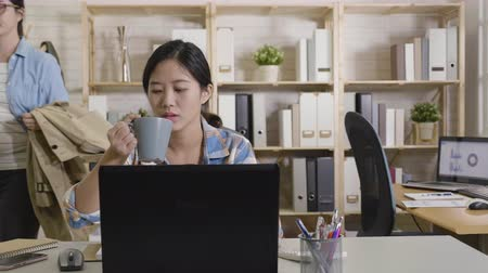 пальто : slow motion of young asian girl employee waving hand saying goodbye to colleague sitting in computer desk drinking water hard working in office. co worker ready to go home after work put on jacket.